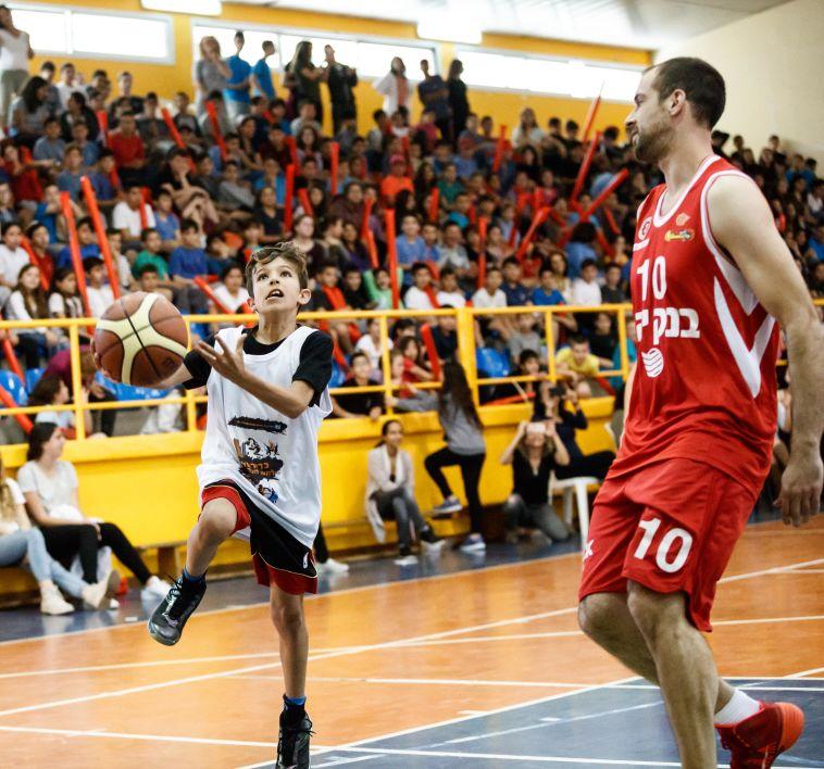 יותם הלפרין נאבק על הכדור עם תלמיד חטיבת הביניים (עודד קרני)