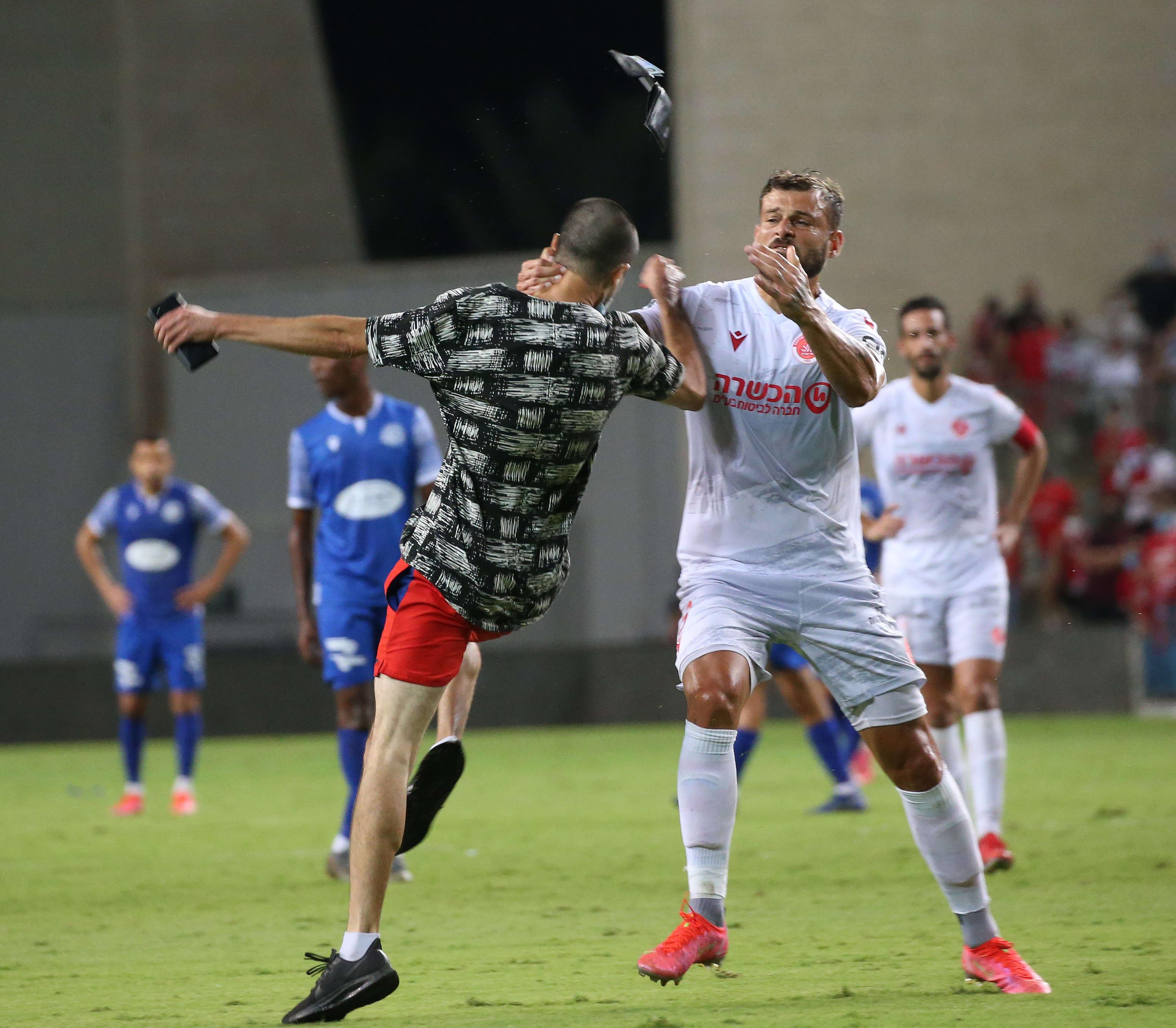 Eddie Gottlieb, a Hapoel Tel Aviv player, next to a fan who attacked him