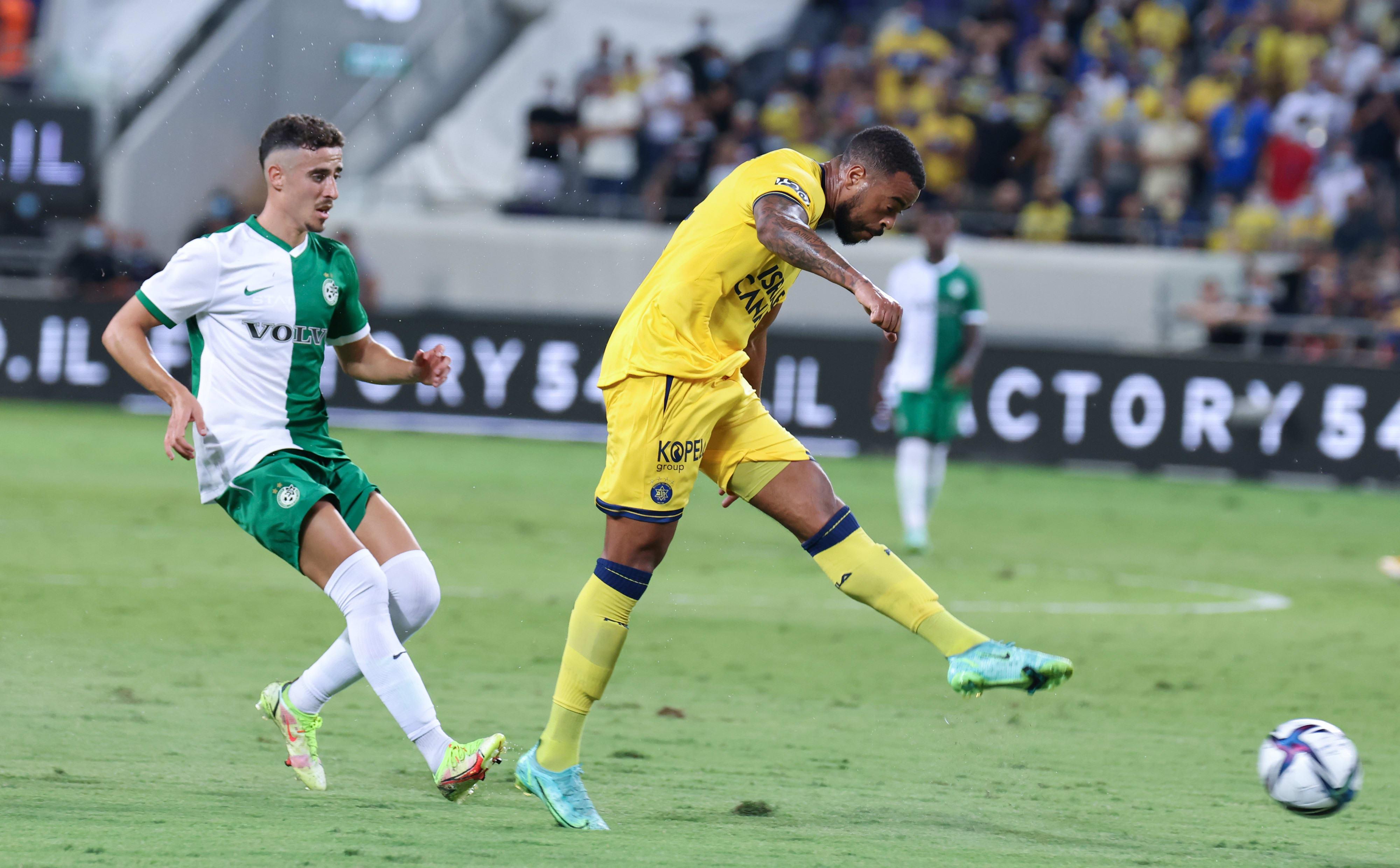 Maccabi Tel Aviv player Brandley Kobas kicks Maccabi Haifa player Dolev Haziza