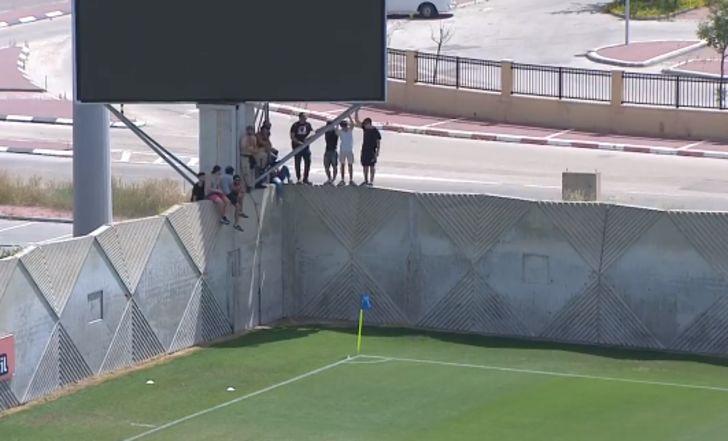 """צפו: אוהדי הפועל ת""""א טיפסו על החומה וצפו במשחק, פתיחת המחצית השנייה התעכבה"""