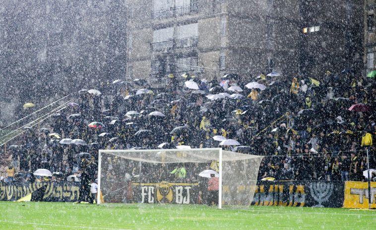 """אוהדי בית""""ר. גשם שוטף באצטדיון הי""""א (דני מרון)"""
